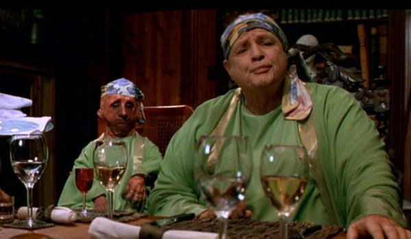 The Island of Dr Moreau Marlon Brando sitting in front of glasses of wine