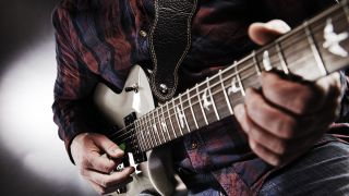 Close-up of hands playing electric guitar