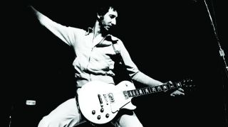 Pete Townshend windmilling his arm while playing guitar.