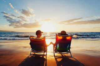 A couple sits in chair on a beach at sunset.