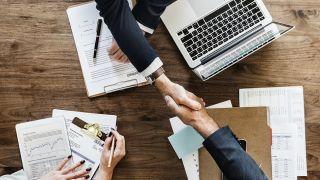 Two men shaking hands across a corporate desk