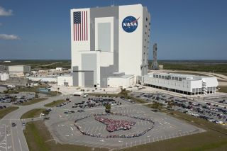 Thousands of NASA Kennedy Space Center employees stand side-by-side to form a full-scale outline of a space shuttle orbiter outside the Vehicle Assembly Building on March 18, 2011.
