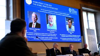 Representatives from the Royal Swedish Academy of Sciences sit in front of a screen displaying the winners of the 2021 Nobel Prize in Physics.