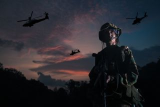 woman soldier looking victorious with apache helicopter fly past.