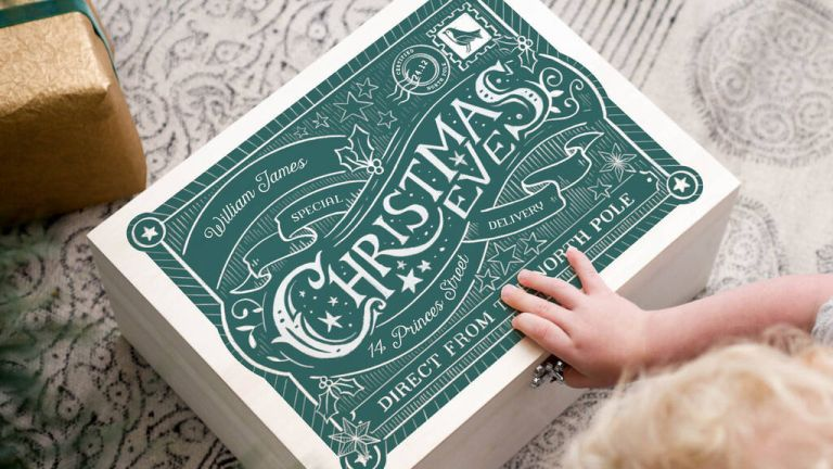 No Ordinary Gift Personalised Christmas Eve Box on floor in green with child's hand on top
