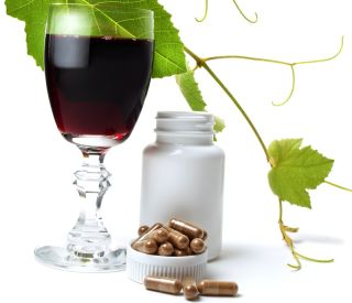 A glass of wine and pills of resveratrol.
