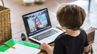 Young boy sat in front of laptop watching teacher