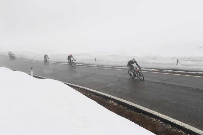 Riders coming through the fog on the top of the Passo Giau during stage 16 of the Giro d'Italia 2021