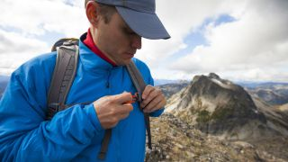 A hiker adjusting the sternum strap on his backpack during a hike