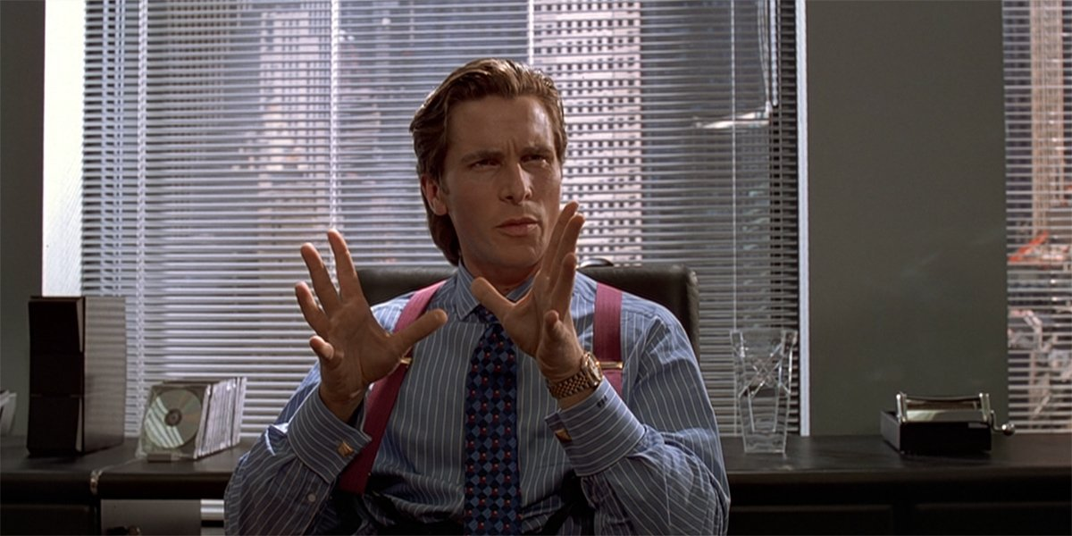American Psycho Christian Bale as Patrick Bateman at desk
