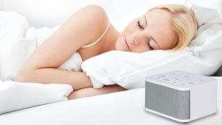 Woman lying in bed next to Red Rooster white noise machine