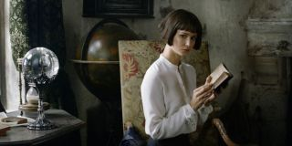 Katherine Waterston reading a book and looking ominously toward the camera in Fantastic Beasts: The Crimes of Grindelwald.