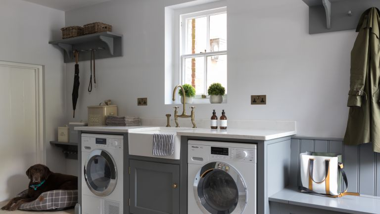 A grey mudroom laundry area with two washing appliances, butlers sink and bench