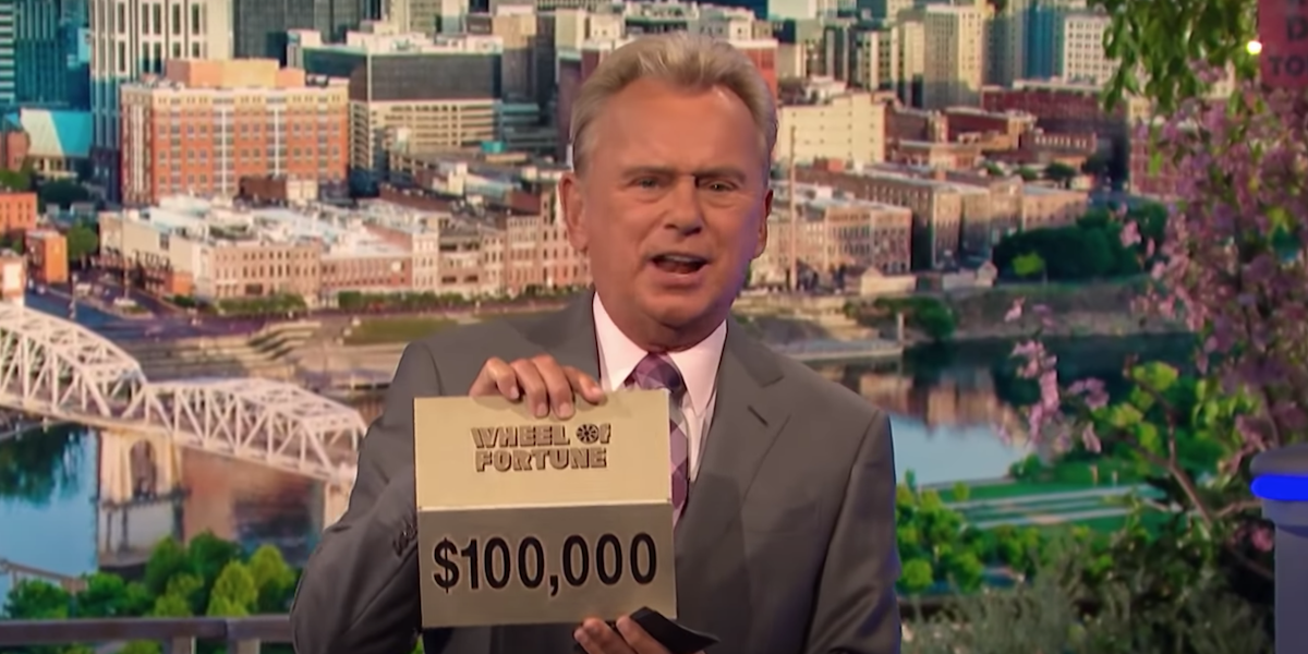 pat sajak holding up $100,000 prize card on wheel of fortune