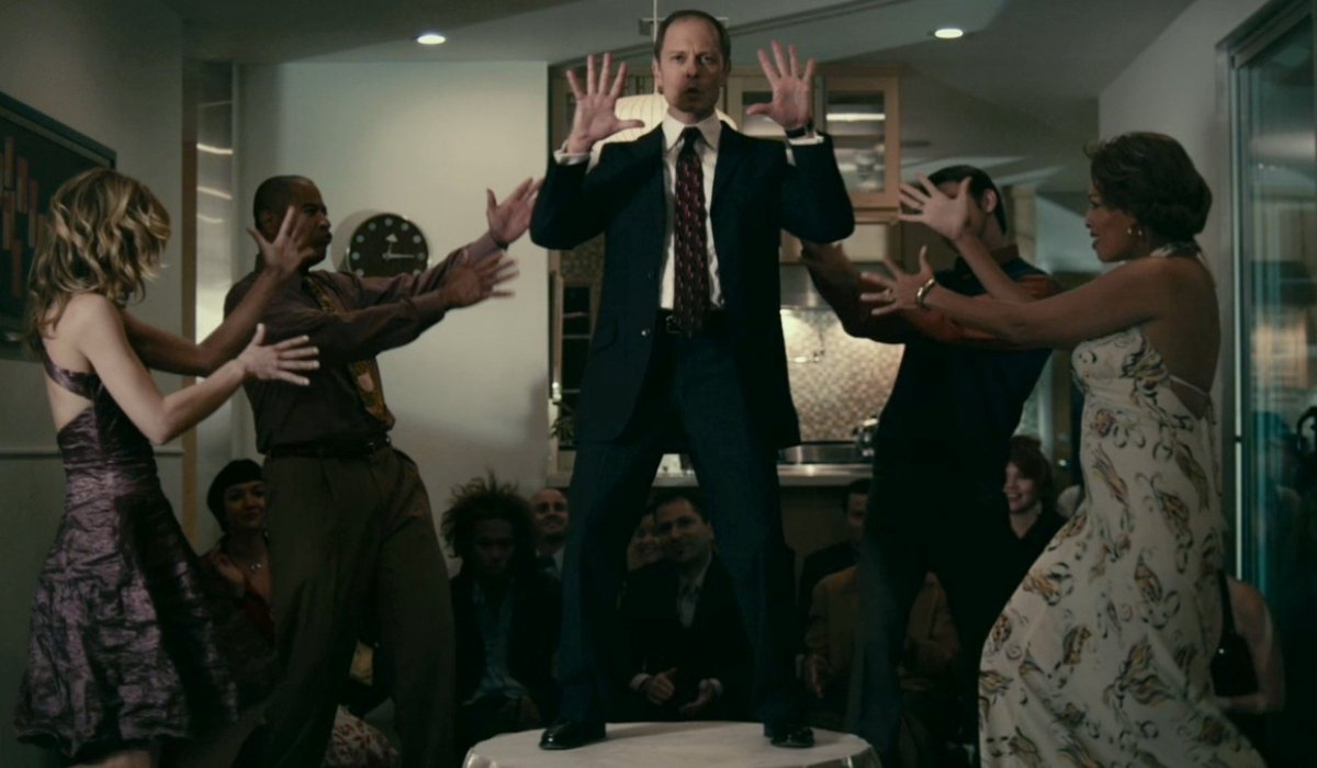 The Perfect Host David Hyde Pierce dances on top of a table, surrounded by friends