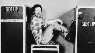 A photograph of Bruce Springsteen with his feet up on some amp boxes