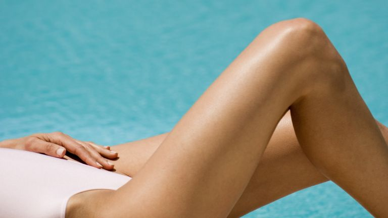 how to fake tan: model lying next to a pool