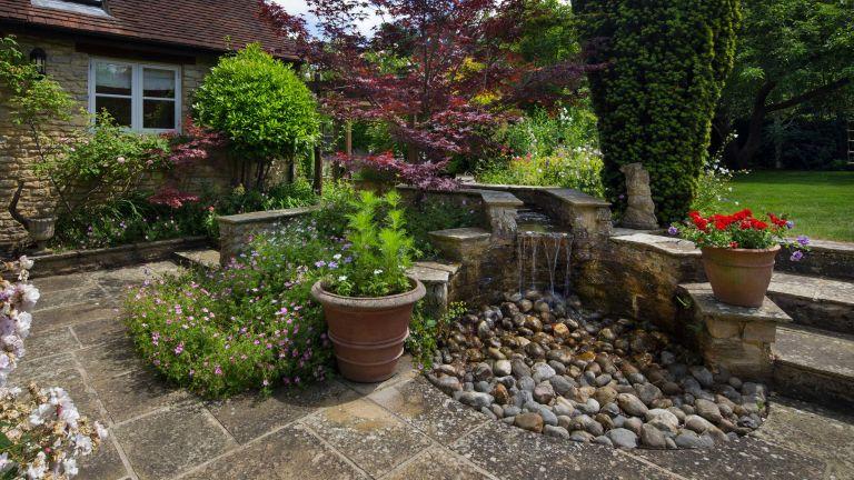 garden decor with stones: stone water feature in english garden