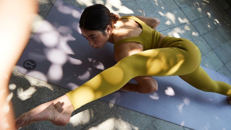 Lululemon Instill tights in gold woman on yoga mat stretching