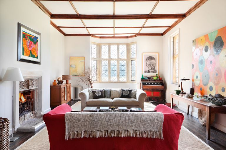 living_room_with_bay_window_beams_fireplace_art