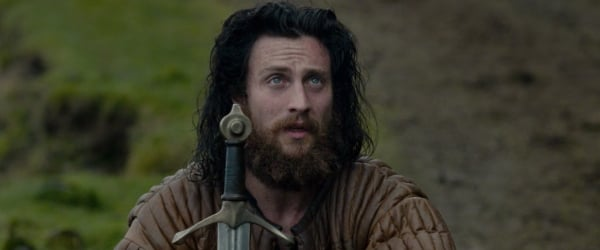Outlaw King Aaron Taylor-Johnson kneeling with a sword held in front of him