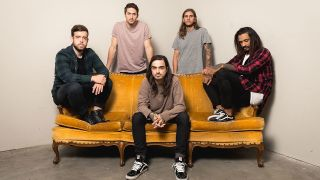 Like Moths To Flames sat on a sofa