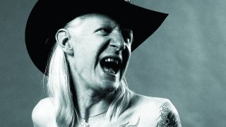 Johnny Winter, yelling, topless, wearing a cowboy hat.