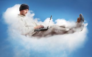 A man sits aloft on a cloud, working on his laptop