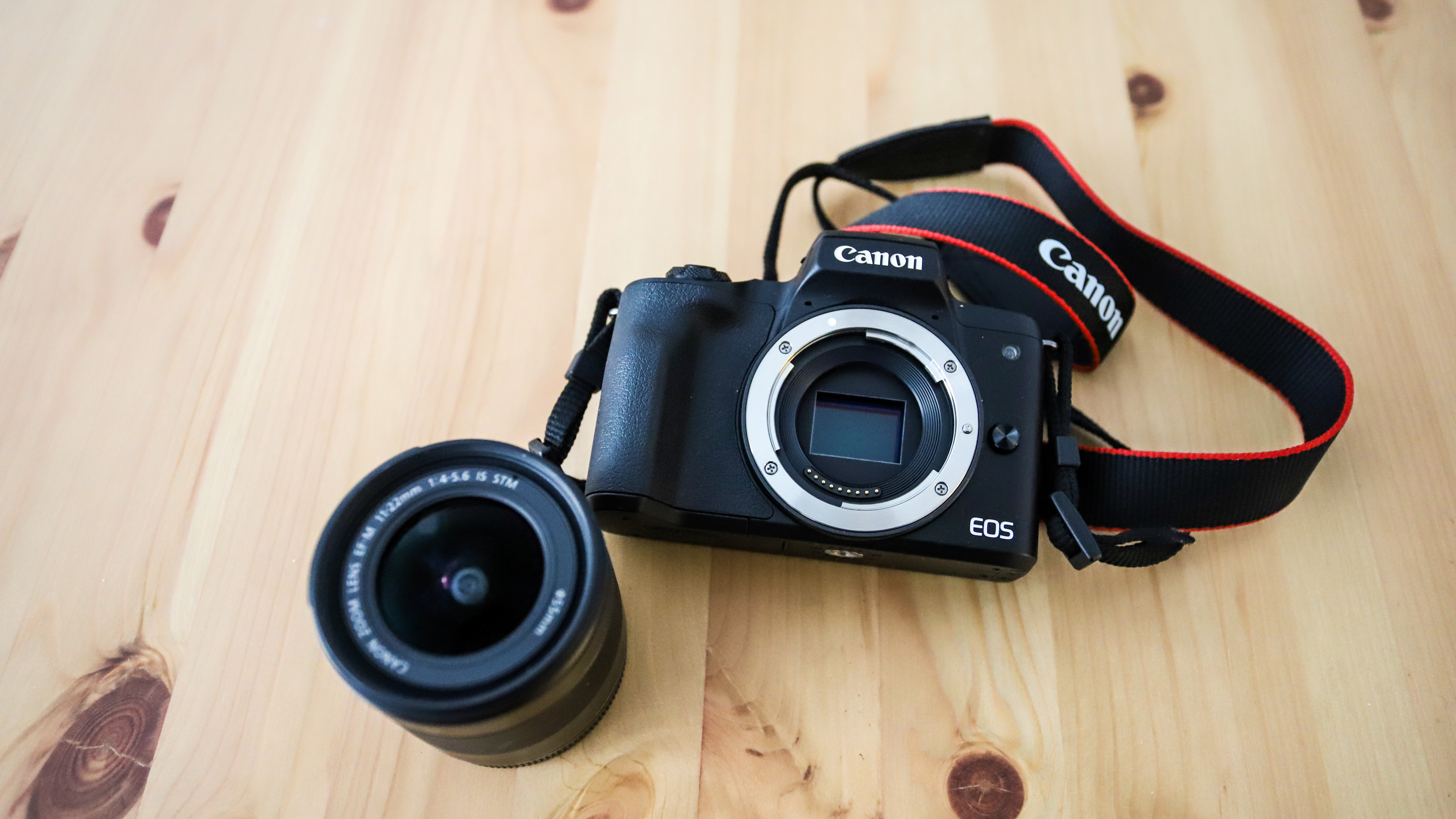 The Canon EOS M50 Mark II on a wooden floor next to a 11-22mm lens.