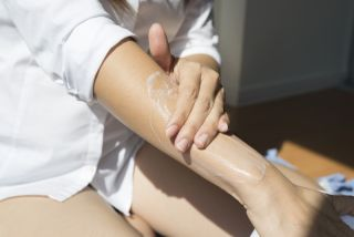 A woman puts lotion on her arm.