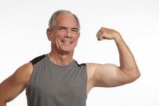 An older man flexes his bicep.