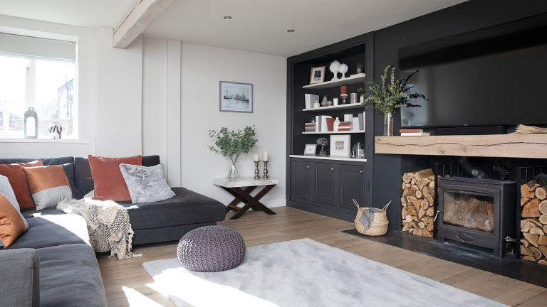 Hutchinson house: living room with black feature wall, large fireplace with woodburner and Scandi-style finishes
