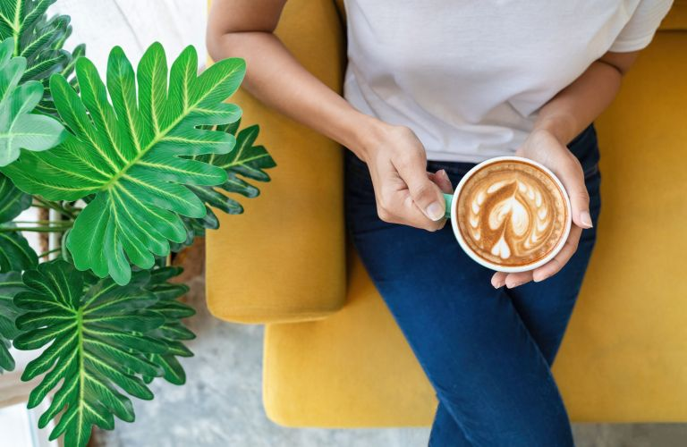 Gifts for coffee lovers woman with coffee cup in lap