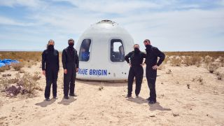 Blue Origin personnel standing in as astronauts during Mission NS-15 pose in front of the New Shepard Crew Capsule after a successful mission on April 14, 2021.