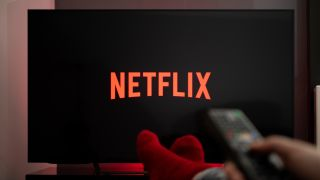 Netflix on TV screen with feet up in front and hand holding remote