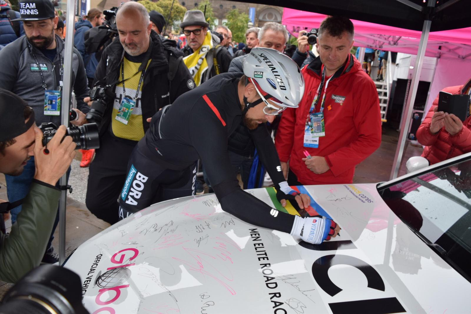 Peter Sagan autographs a race car