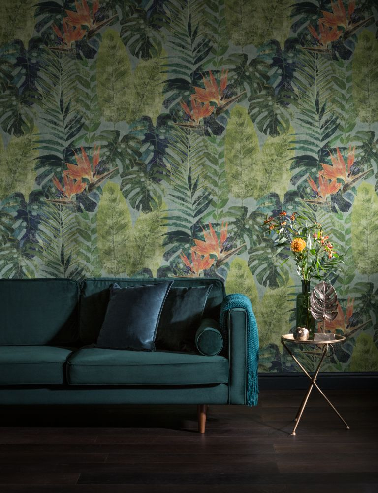 tropical leafy wallpaper in living room with pops of orange and greeny blue velvet sofa
