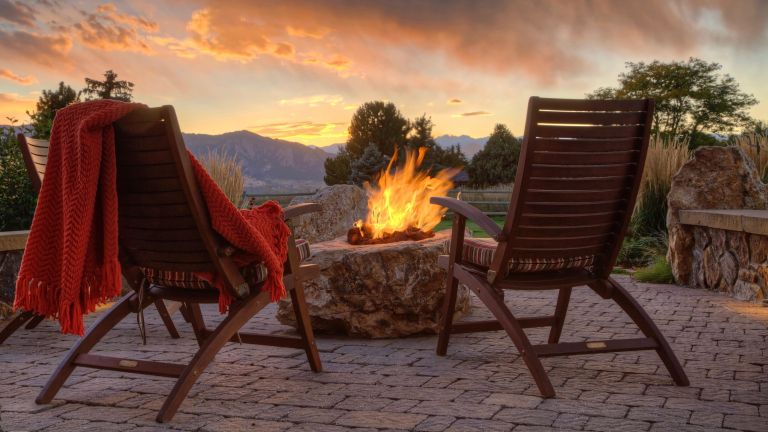 Two armchairs alongside DIY fire pit ideas on a patio at sunset
