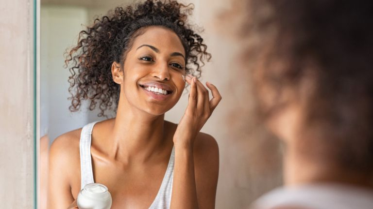 Woman applying eye cream and smiling in the mirror