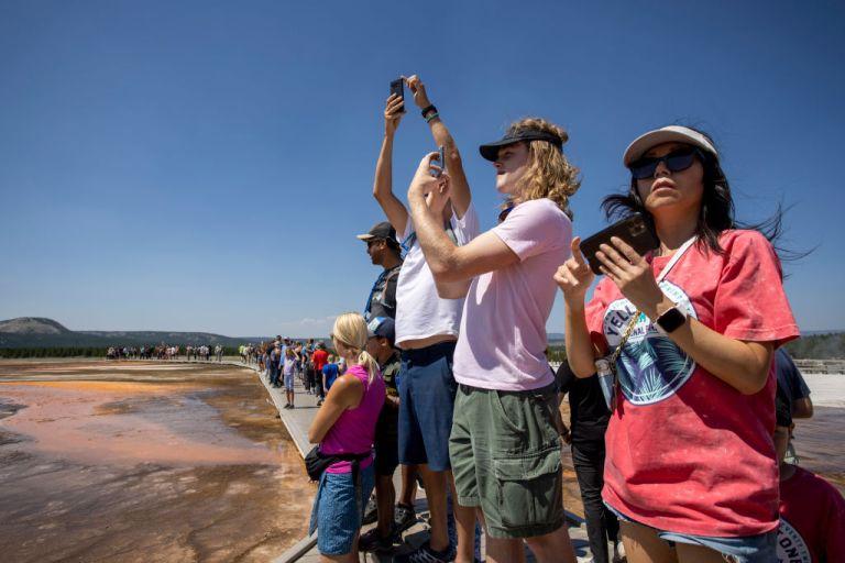 tourists take photos at yellowstone national park