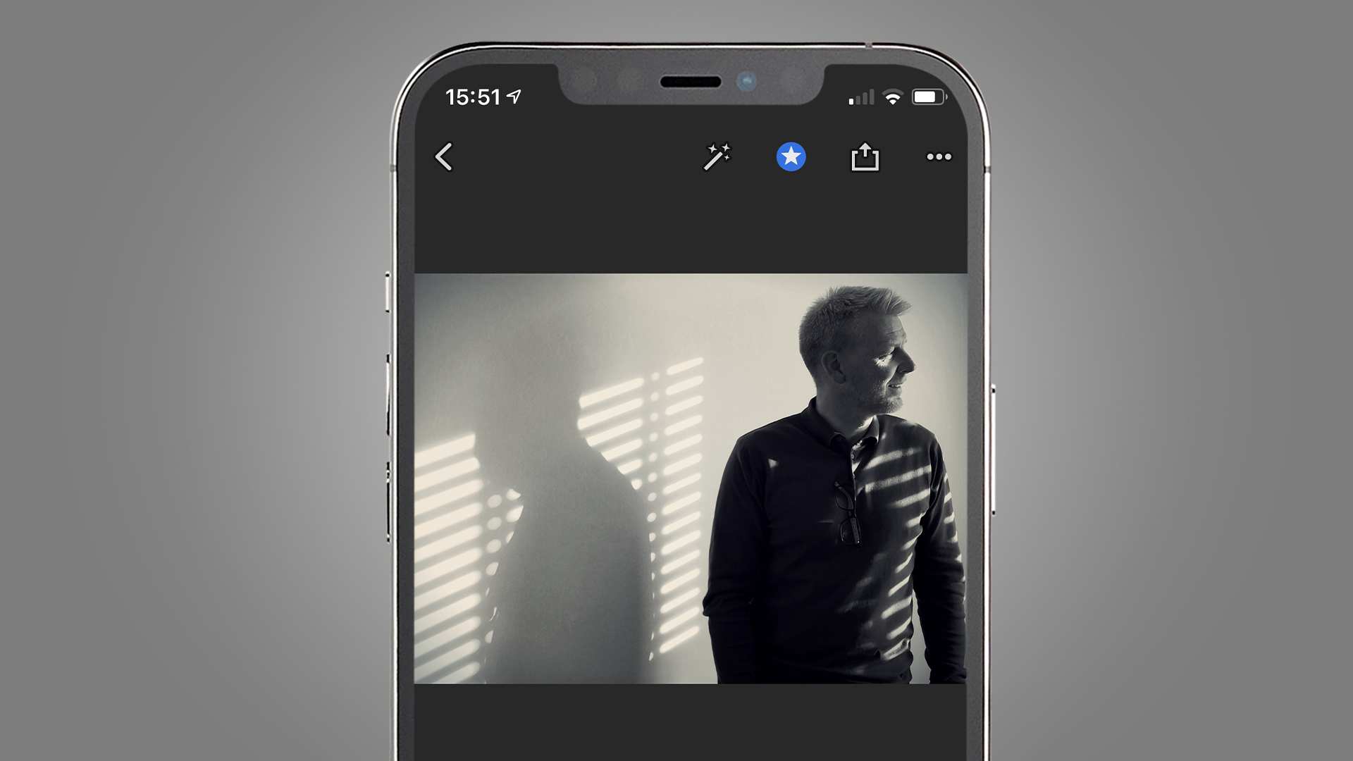 A phone screen showing a portrait of a man looking through a window