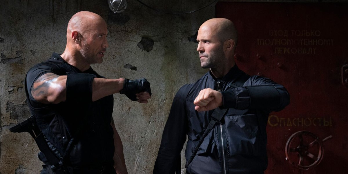 Hobbs (Dwayne Johnson) and Shaw (Jason Statham) check watches in Hobbs and Shaw