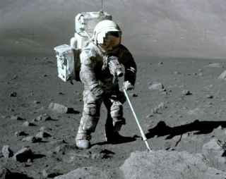 Apollo 17 astronaut Harrison Schmitt retrieves lunar samples during his December 1972 mission, his spacesuit dirtied by clinging lunar dust.