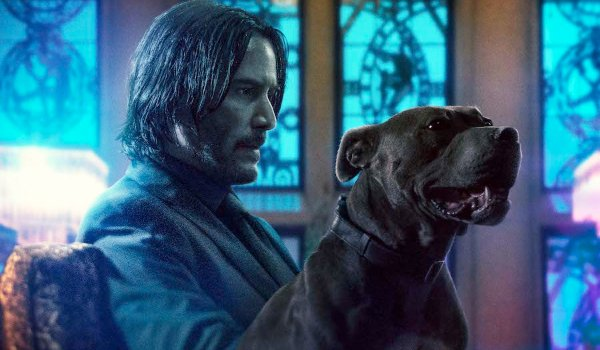 John Wick: Chapter 3 John and his dog sitting on a couch in the lobby