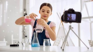 Pre-teen girl recording an interesting chemical experiment and mixing chemicals, pouring a pink one into the water