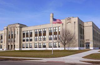 U.S. high school building with American flag.