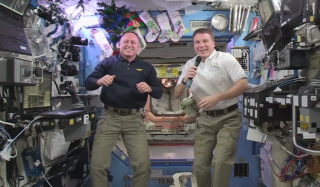 """NASA astronaut Barry """"Butch"""" Wilmore (left) floats with ESA astronaut Samantha Cristoforetti (center) and NASA's Terry Virts (right) record a New Year's greeting on the International Space Station for people on Earth."""