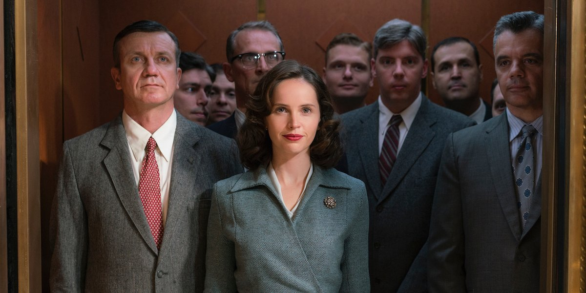 Ruth Bader Ginsburg (Felicity Jones) smiles while standing in an elevator full of men in 'On The Basis of Sex'
