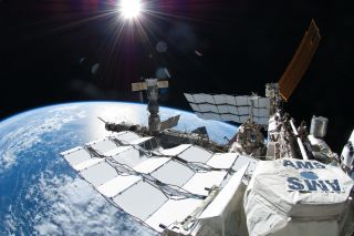 A photo of the Alpha Magnetic Spectrometer (AMS) experiment outside the International Space Station. NASA astronaut Ron Garan took this photo during a spacewalk on July 12, 2011. The space shuttle Atlantis is docked at the edge of the frame on the far right, and a Russian Soyuz spacecraft is docked to Pirs, below the sun.