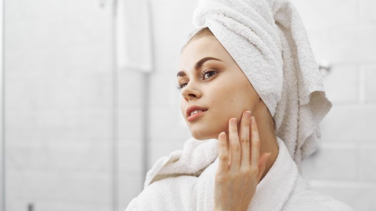 A woman applies face cream in her bathroom